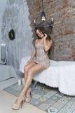 Красивая leggy молодая сексуальная элегантная девушка с большими грудями, носящ гениальное плотное платье и шпильки sensually сид стоковое изображение