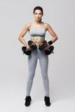 Красивая sportive девушка в sportswear смотря straigth камеры держа большие гантели над белой предпосылкой Стоковая Фотография