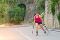 Красивая sporty белокурая девушка с Rollerblade и взбираясь ручкой стоковая фотография