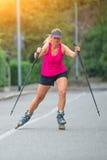 Красивая sporty белокурая девушка с Rollerblade и взбираясь ручкой стоковая фотография rf