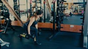 Красивая sporty женщина брюнет средних лет делая тренировки с гантелями в спортзале видеоматериал