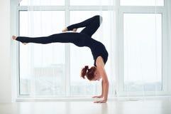 Красивая sporty женщина yogi пригонки практикует asana Bhuja Vrischikasana handstand йоги - представление handstand скорпиона на  стоковые фото