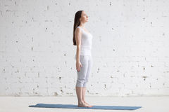 Красивая sporty молодая женщина делая представление Tadasana в белую просторную квартиру стоковое изображение rf
