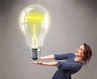 Красивейшая дама держа реалистическую электрическую лампочку 3d Стоковое фото RF