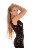 Красивейшая белокурая женщина в черном глянцеватом платье Стоковая Фотография