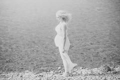красивейшая беременная женщина Беременная женщина в белом платье идя на пляж моря Стоковое Фото