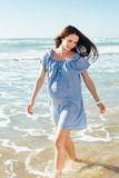Красивейшая беременная женщина гуляя на голубой пляж Стоковое Изображение