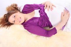 Красивейшая беременная женщина лежит на белой шерсти стоковые фотографии rf