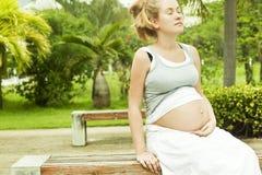 Красивейшая беременная женщина ослабляя на стенде Стоковые Фото