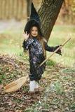Красивейшая ведьма девушки маленькая девочка в которой костюм празднует хеллоуин внешний и имеет потеху Фокус или обрабатывать де стоковые изображения rf