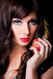 Красивейшая девушка брюнет с яблоком на черноте Стоковое Изображение RF