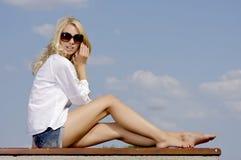 Красивейшая девушка в солнечных очках на голубом небе Стоковое фото RF
