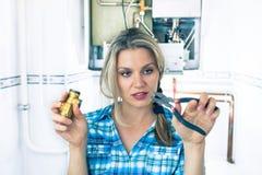 Красивейшая девушка пробует отремонтировать боилер стоковое фото rf