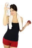 Красивейшая девушка спорта с водой и яблоко в руках Стоковое Изображение