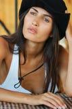 Красивейшая длинн-с волосами женщина типа страны в черной шляпе и джинсыах сидя в стуле wicker Стоковые Изображения