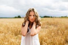 красивейшая девушка поля смотрит усмешки вверх по детенышам пшеницы Стоковые Фото