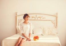 Красивейшая девушка сидя на кровати стоковая фотография