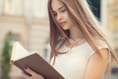 красивейшая девушка outdoors читая Стоковое Фото