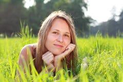 красивейшая женщина портрета зеленого цвета травы лежа Стоковое Изображение RF