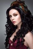 красивейшая женщина портрета Молодая дама представляя на серой предпосылке с пер в волосах Стоковые Фото