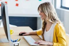 Красивейшая женщина работая на компьютере стоковое фото