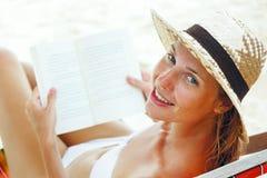Красивейшая женщина сидя на пляже читая книгу Стоковые Фото