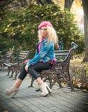 Красивейшая женщина способа сидя на стенде парка Стоковая Фотография RF