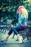 Красивейшая женщина способа сидя на стенде парка Стоковая Фотография