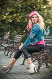 Красивейшая женщина способа сидя на стенде парка Стоковые Изображения