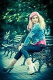 Красивейшая женщина способа сидя на стенде парка Стоковое фото RF