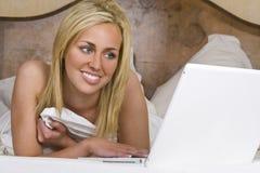 красивейшая компьтер-книжка компьютера кровати используя женщину стоковые изображения rf