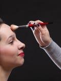 Красивейшая молодая женщина брюнет прикладывая порошок с щеткой стоковое изображение rf