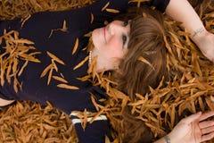 Красивейшая молодая женщина лежа в листьях Стоковая Фотография