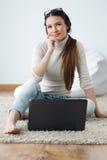 Красивейшая молодая женщина работая на ее компьтер-книжке на дому Стоковая Фотография