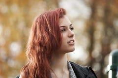 Молодая женщина с красивейшими каштановый волосами с предпосылкой осени стоковые фото