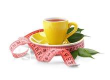 красивейшая потеря принципиальной схемы живота над женщиной веса белой Изолированные чашка чаю и измеряя лента стоковое фото rf