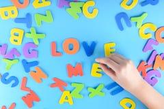 Красивейшая предпосылка Девушка кладет из пестротканых писем слова любят меня Стоковые Изображения RF
