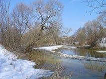 красивейшая природа ландшафта Поток весны слякоть Расплавленный снег переполнение Голубое небо и дома на предпосылке Стоковое Фото