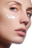 Красивейшая сторона молодой женщины с косметической сливк на щеке Принципиальная схема внимательности кожи Портрет крупного плана Стоковое Изображение RF