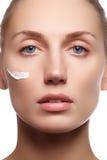 Красивейшая сторона молодой женщины с косметической сливк на щеке Принципиальная схема внимательности кожи Портрет крупного плана Стоковое Фото