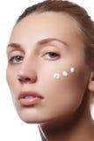 Красивейшая сторона молодой женщины с косметической сливк на щеке Принципиальная схема внимательности кожи Портрет крупного плана Стоковые Фотографии RF