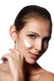 Красивейшая сторона молодой женщины с косметической сливк на щеке Sk Стоковое Изображение