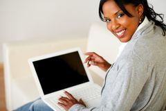 Красивейшая черная женщина работая на компьтер-книжке Стоковые Фото