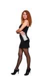 Красивейшая red-haired женщина в черных платье и clut стоковое фото