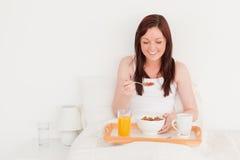 Красивейшая red-haired женщина имея ее завтрак стоковая фотография