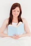 Красивейшая red-haired женщина читая книгу стоковое изображение rf