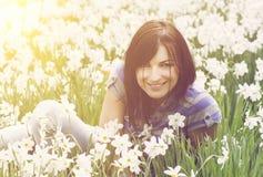 Красивейшее брюнет сидя среди daffodils стоковое фото rf