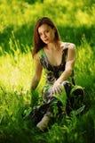 Брюнет сидя на зеленой траве стоковое изображение rf