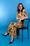 Красивейшее брюнет с стеклами и желтым платьем на сини Стоковые Фотографии RF
