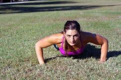 красивейшее брюнет 2 делает outdoors pushups Стоковые Фотографии RF